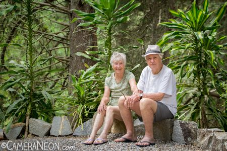 Grandparents sitting by the trail smiling